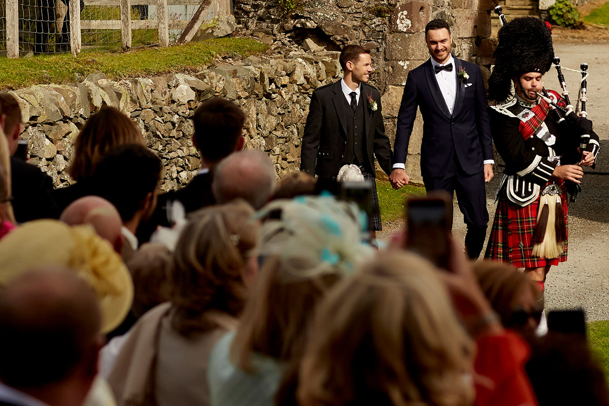 two grooms piped in to wedding ceremony Neidpath Castle