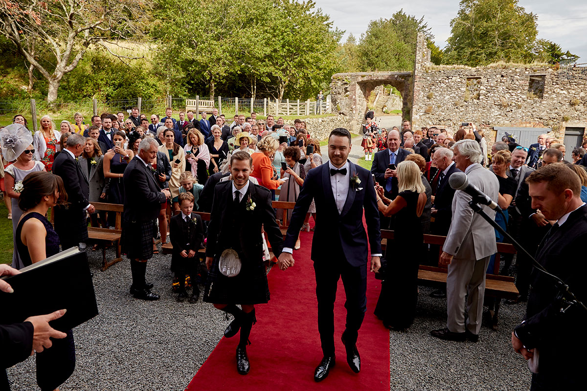 Story of Love Photography two grooms walking down red carpet aisle Neidpath Castle