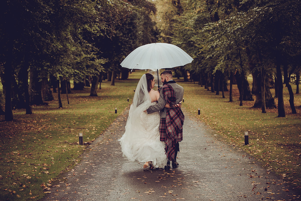 bride and groom in rain at Carlowrie Castle