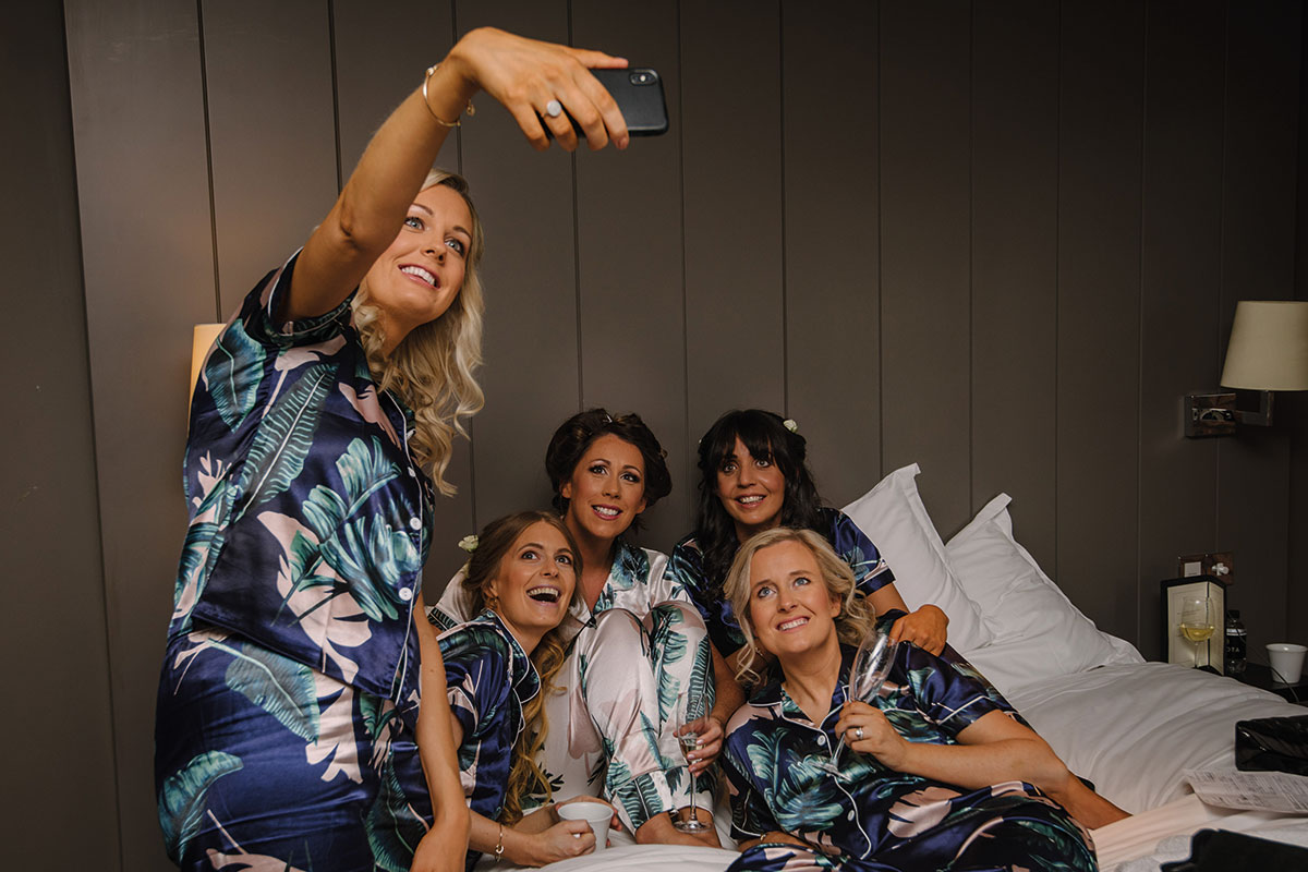 bride with bridesmaids on bed taking selfie