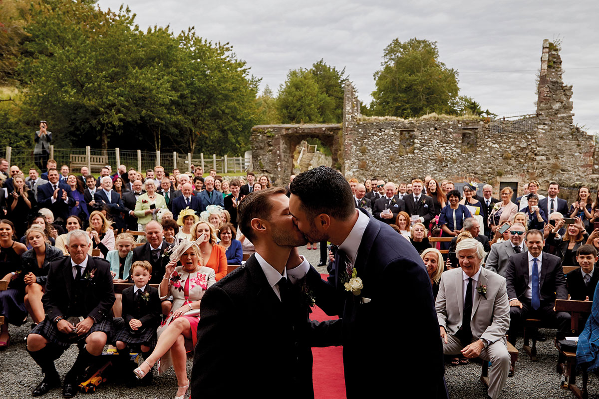 Story of Love Photography two grooms kissing at Neidpath Castle