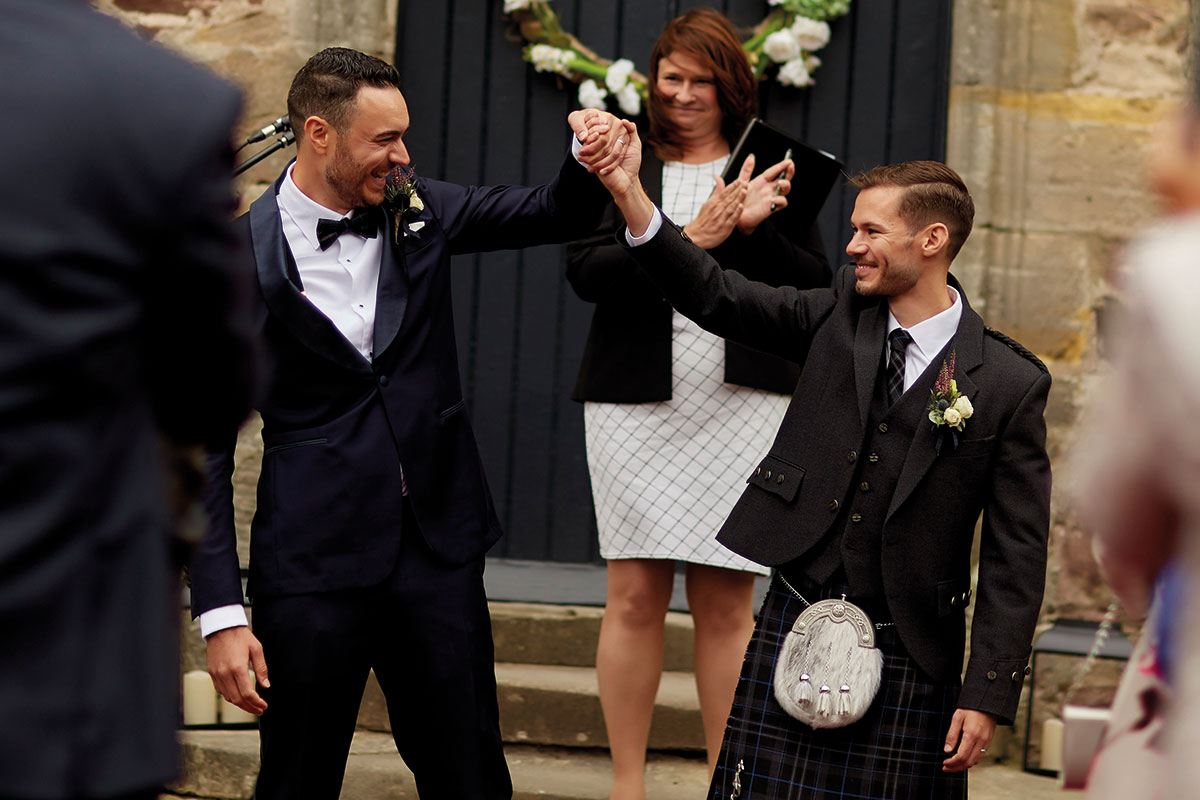 Story of Love Photography two grooms raising hands