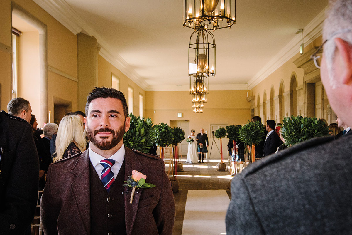 groom waiting on bride being given away by dad