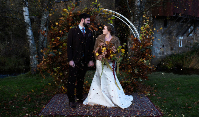 Bride and groom under an autumnal arch