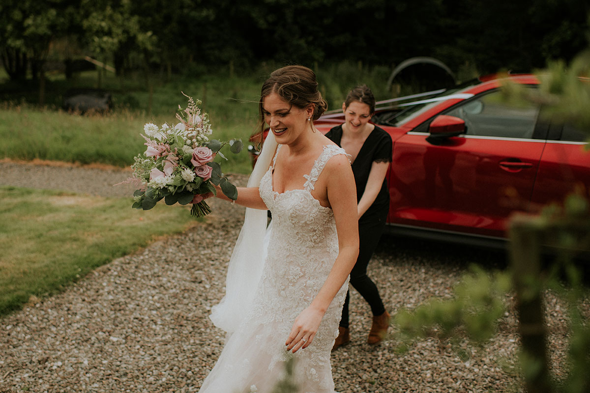 bride walking on path carrying bouquet at fruin farm with person carrying train