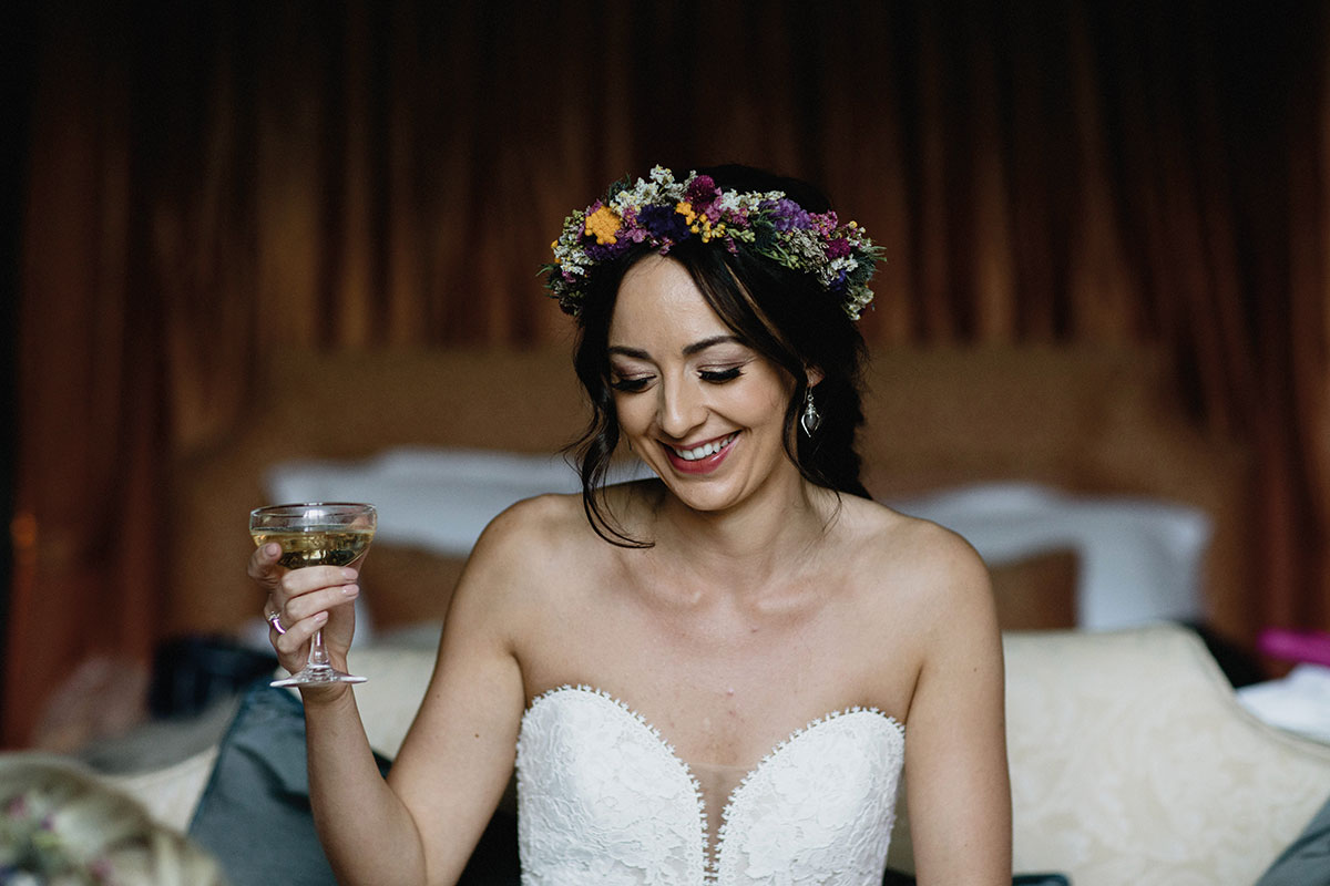bride wearing floral crown holding champagne coupe