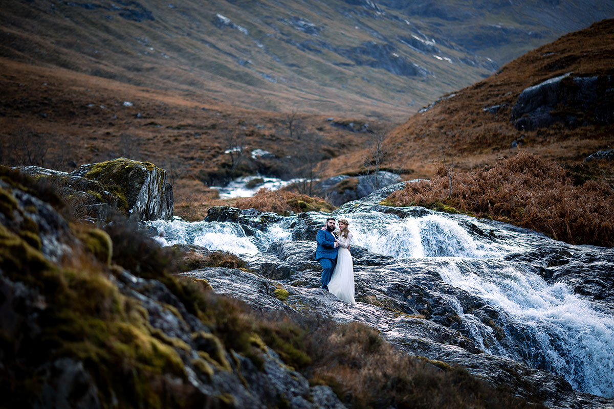 bride and groom on rock by waterfall Glencoe elopement