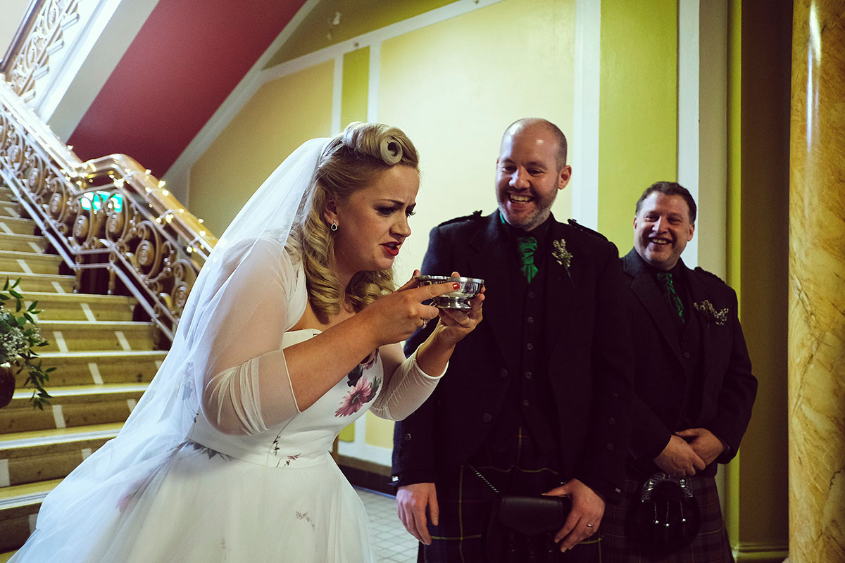 bride drinking from quaich groom laughing
