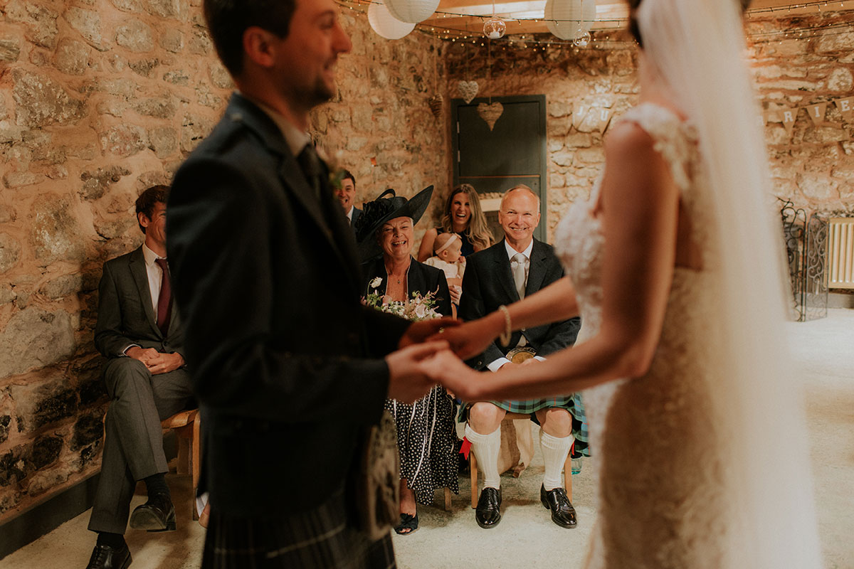 barn wedding ceremony with bride and groom holding hands and seated guests looking on
