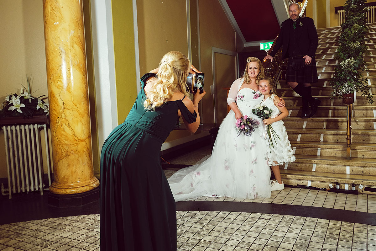 bridemaid taking photo of bride groom and flower girl at Leith Theatre