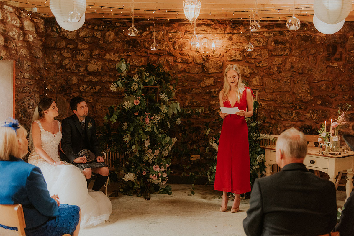 wedding guest wearing red dress doing reading at barn wedding