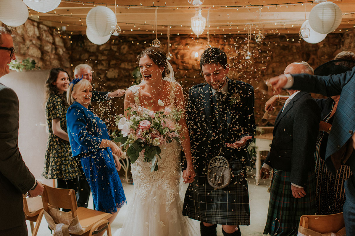 bride and groom showered in confetti walking up aisle at fruin farm