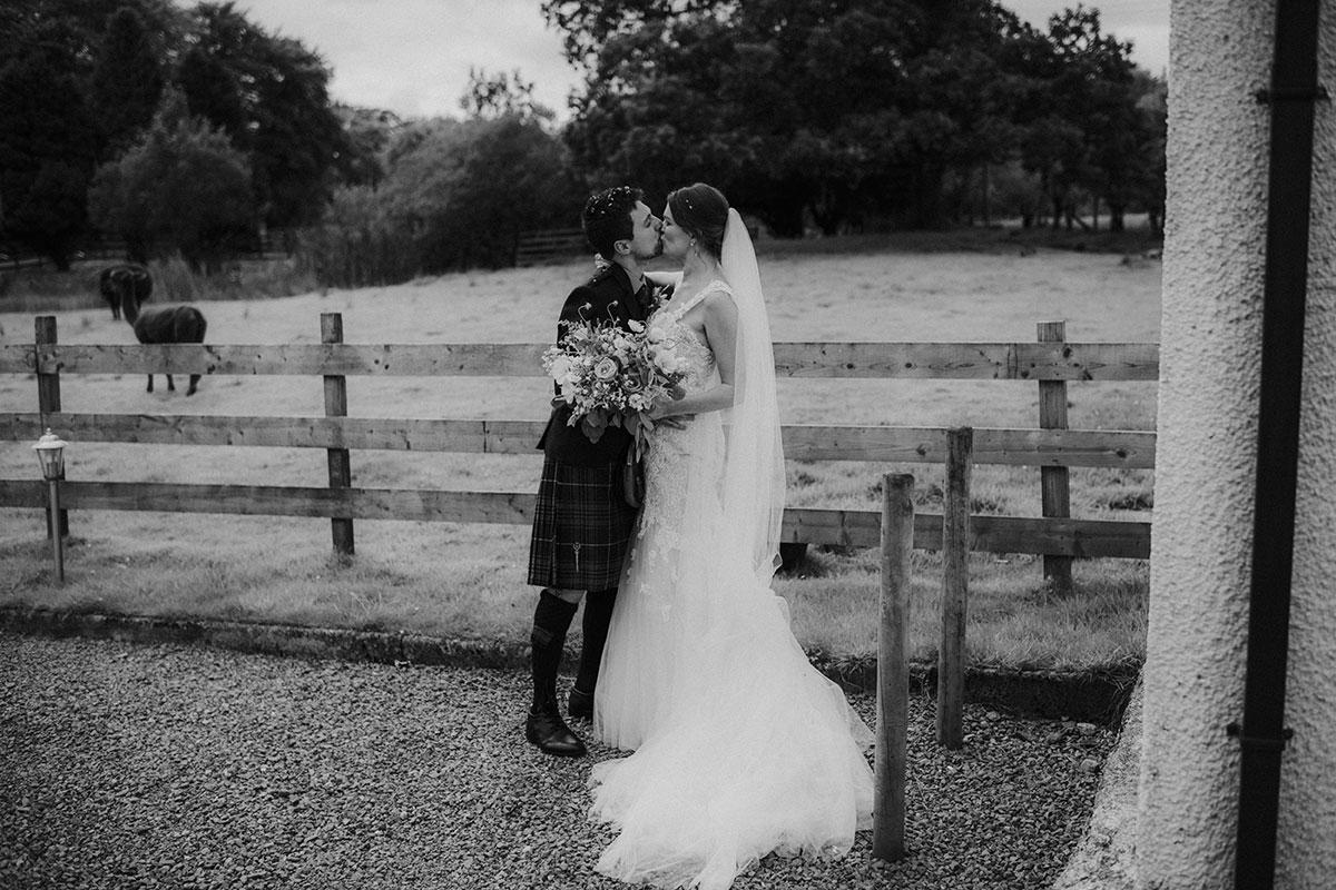 bride and groom kiss beside field at fruin farm