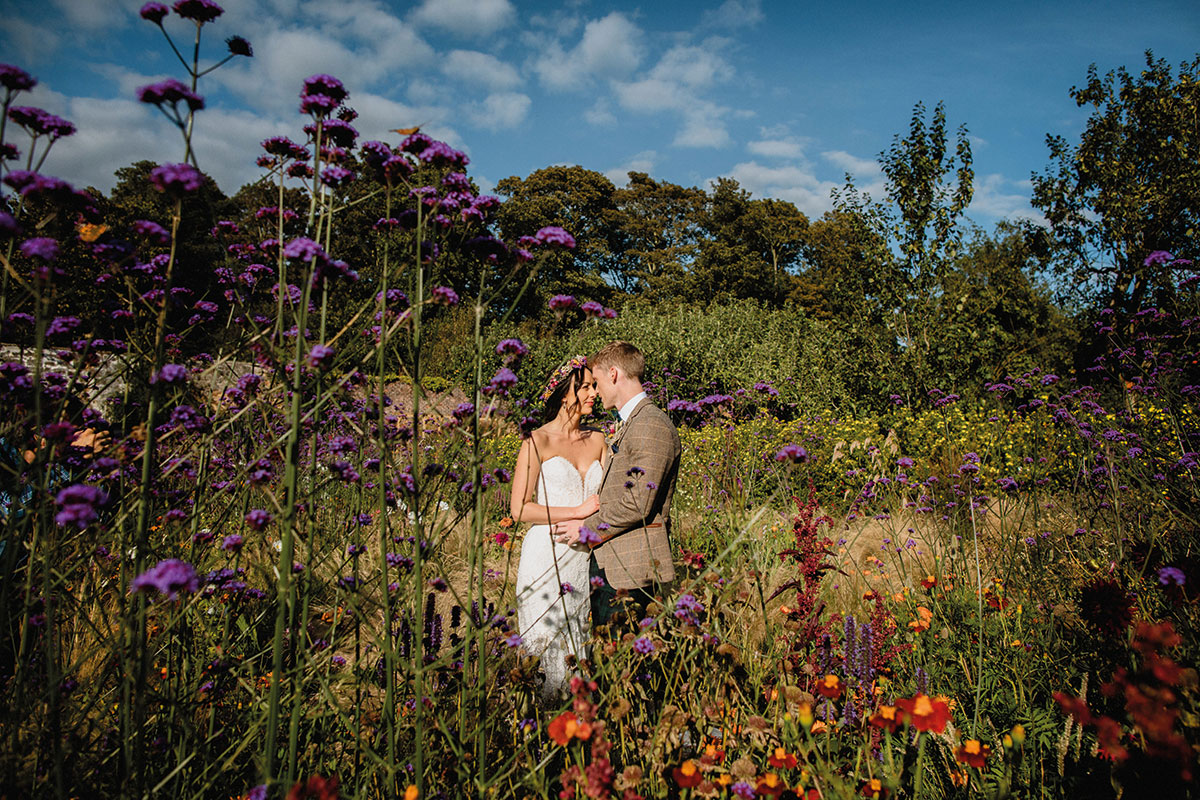 bride and groom surrounded by flowers in a garden