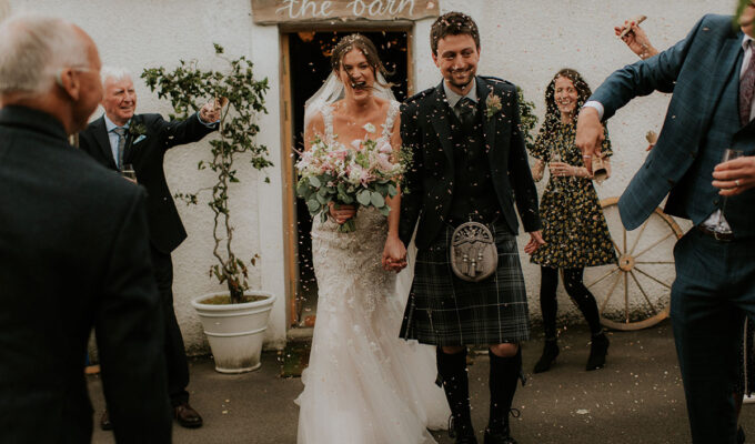 guests throw confetti and newlywed couple outside the barn at fruin farm