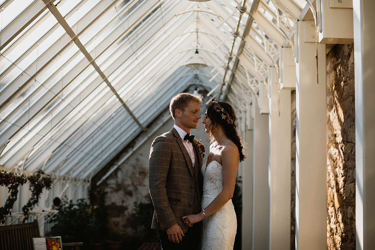 bride and groom in a greenhouse at Cambo Estate