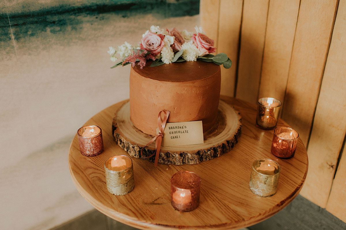 grandma's homemade chocolate wedding cake on table decorated with tea lights and pink roses
