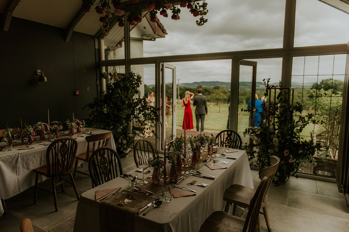 wedding room set for dinner at fruin farm with guests outside open glazed windows