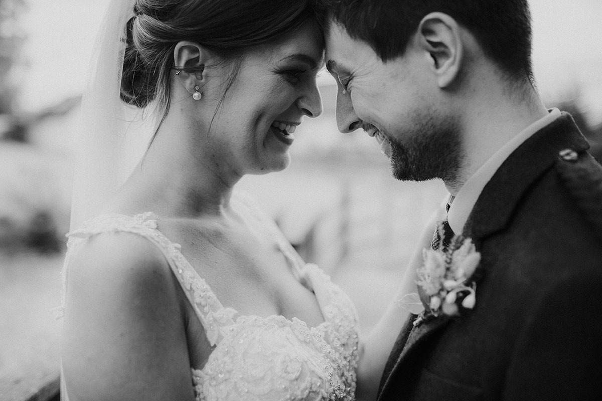 bride and groom smiling forehead to forehead