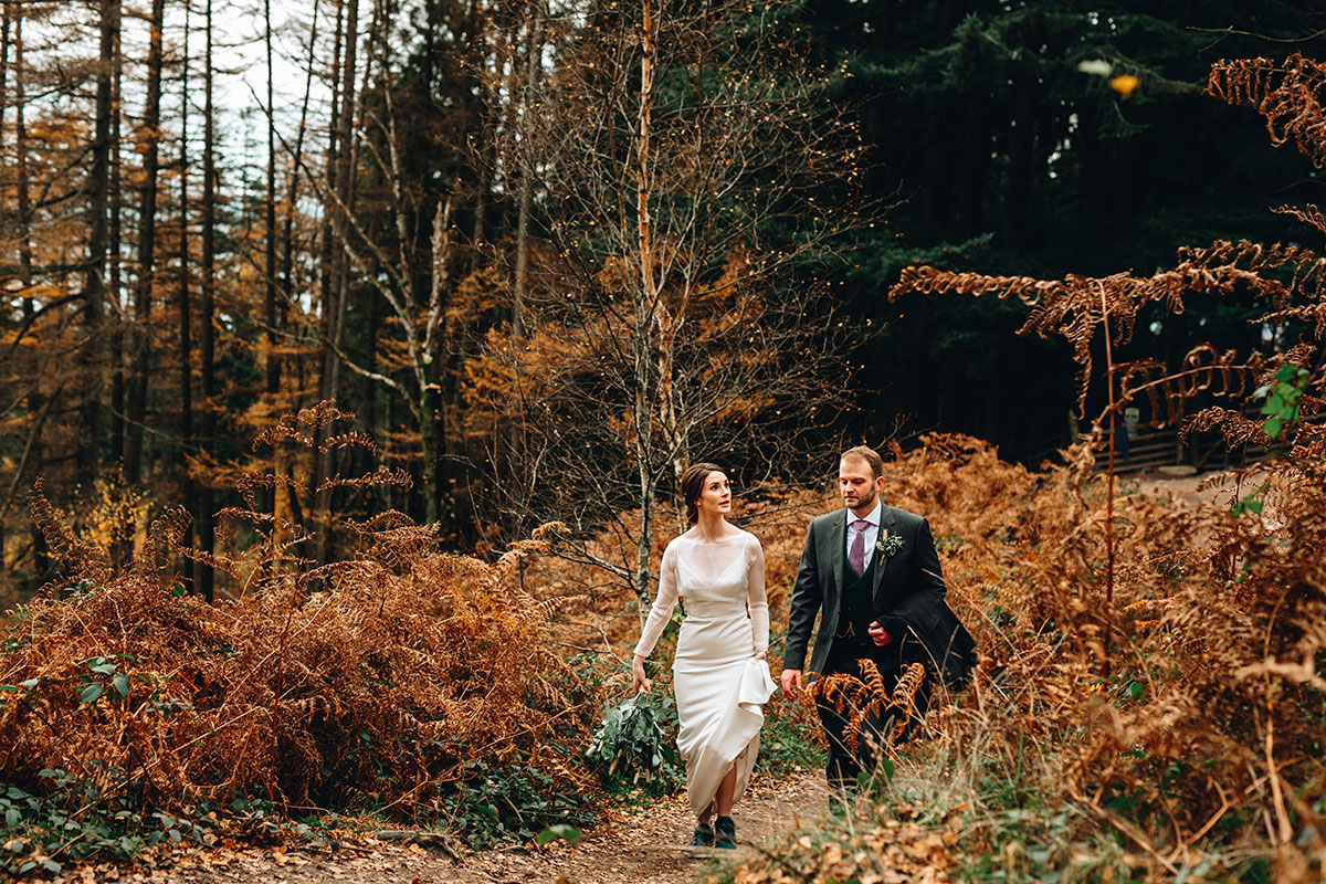 bride and groom walk to the top of Conic Hill Loch Lomond surrounded by autumn bracken