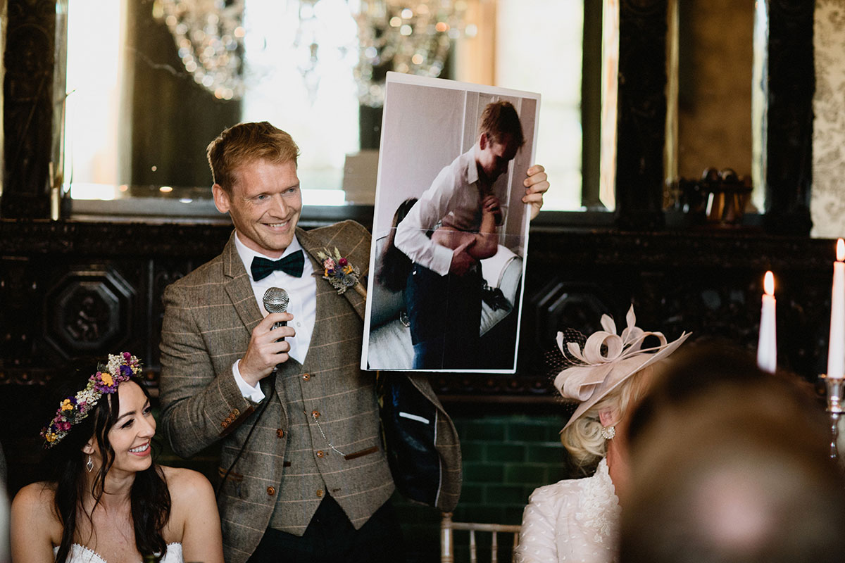 groom holding picture during wedding speech