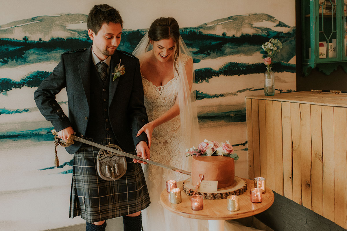 bride and groom cutting homemade chocolate cake with a sword