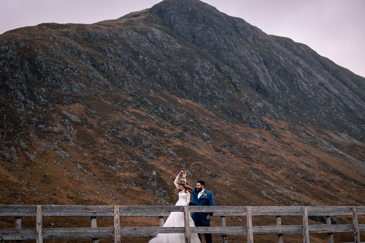 bride and groom dancing on bridge in Glencoe