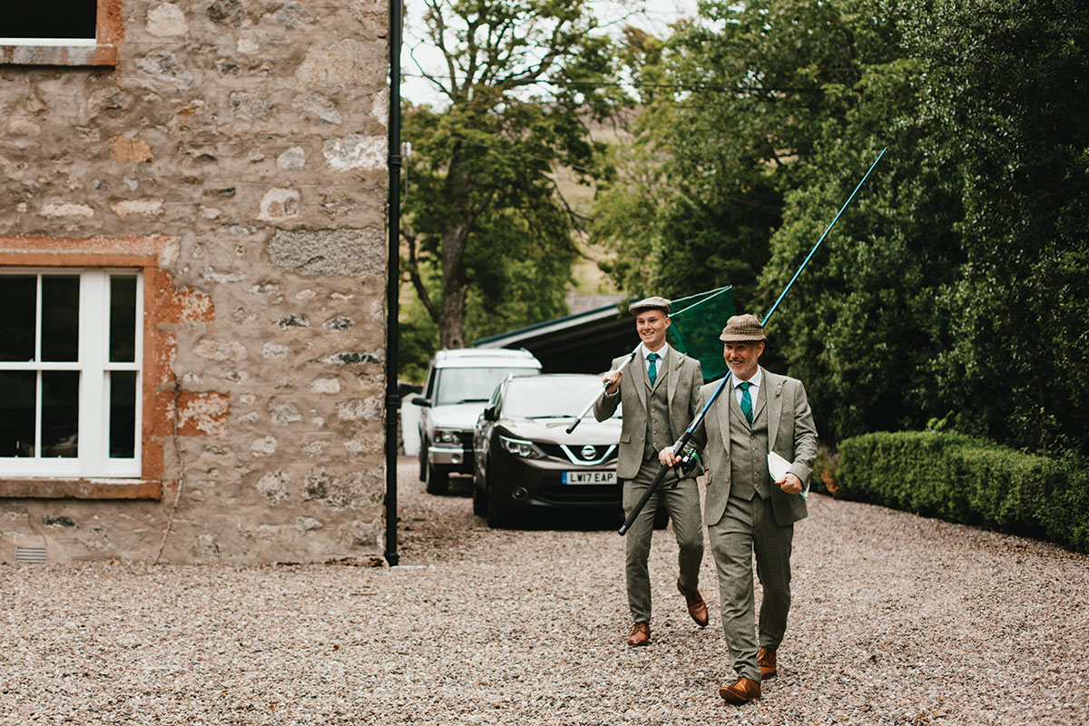 wedding guests wearing tweed suits carrying fishing rods