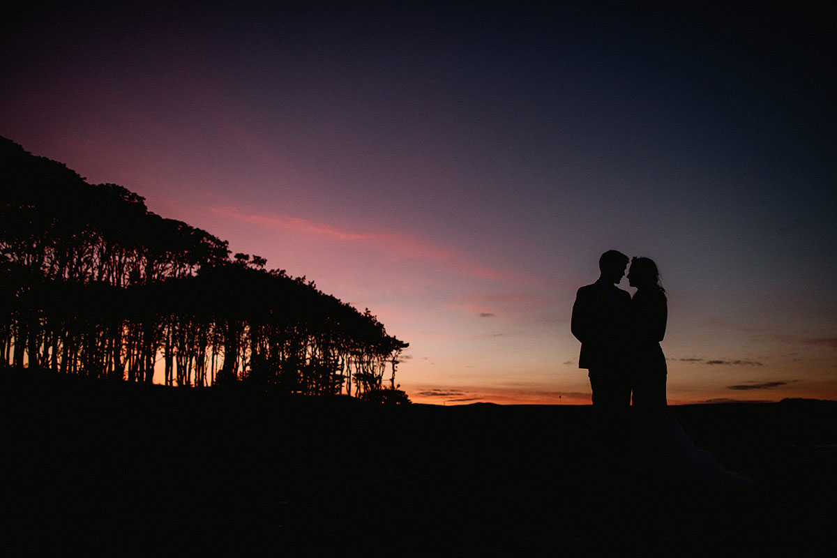 bride and groom silhouette against sunset at Cambo Estate