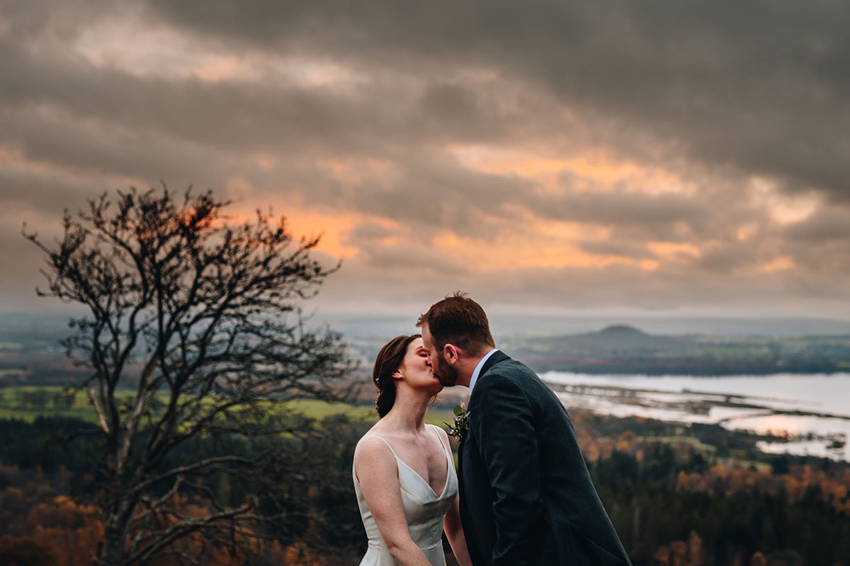 bride and groom kiss on the top of Conic Hill Loch Lomond