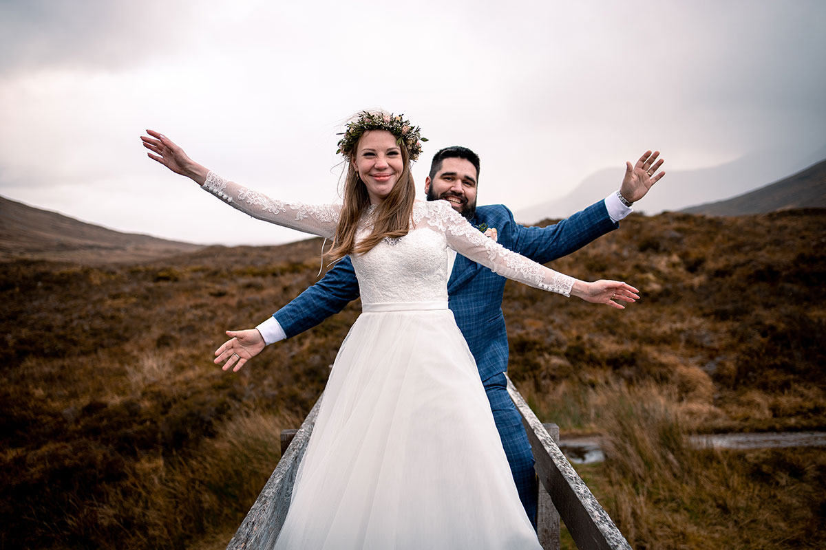 bride and groom on bridge in Glencoe hands in air