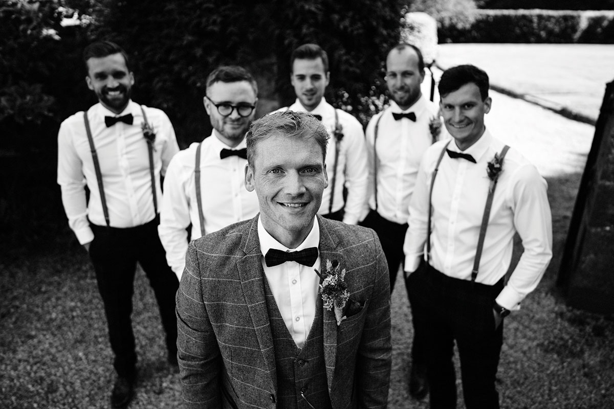 groom with ushers wearing bow ties and braces