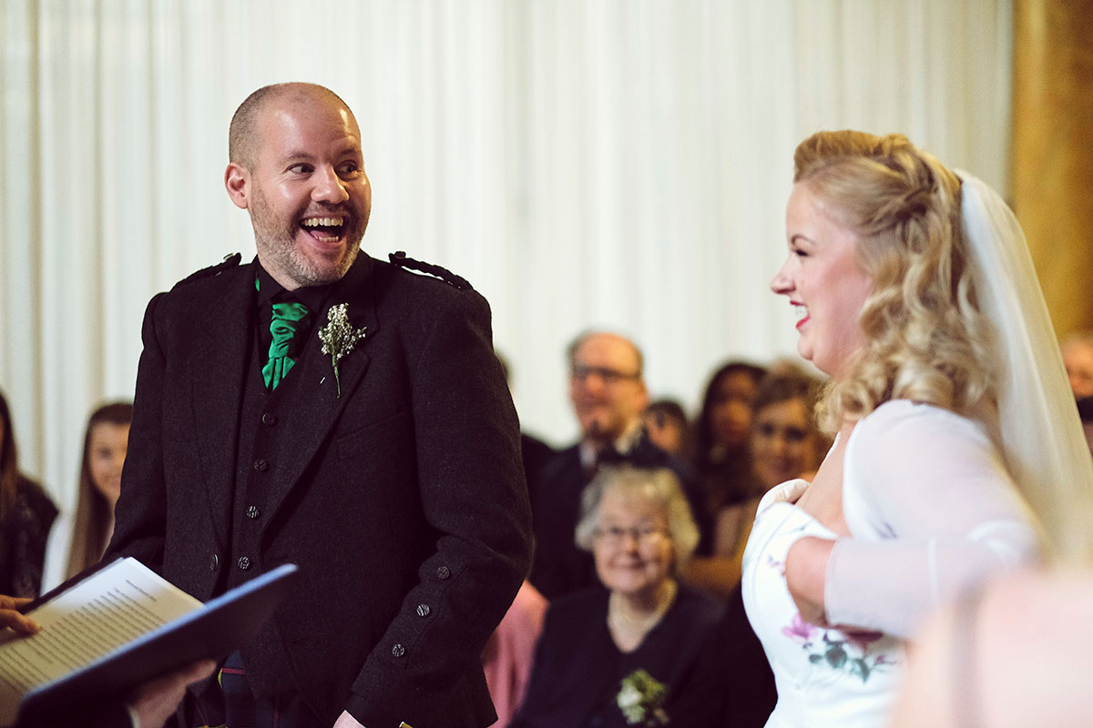 bride and groom laughing during wedding ceremony at Leith Theatre