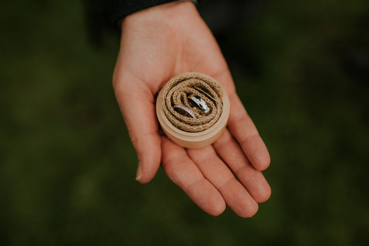 open hand holding wedding rings in raffia and wooden ring box