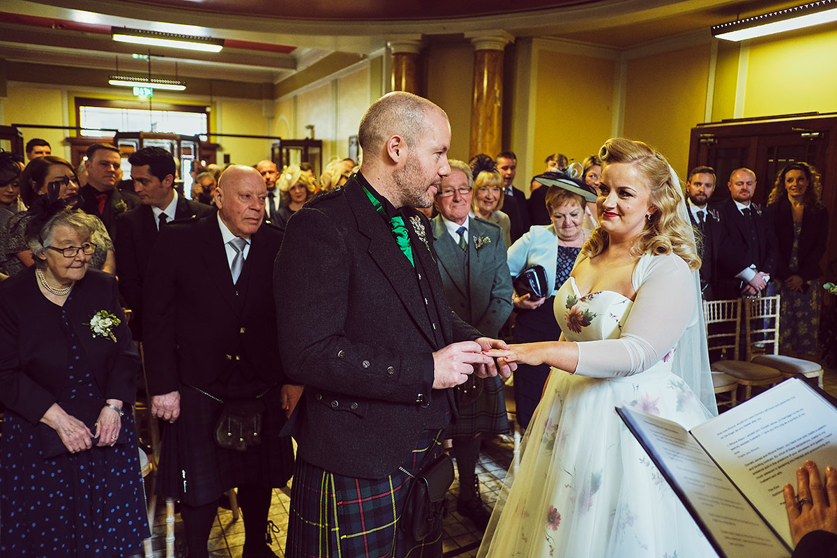 bride and groom exchanging rings at wedding at Leith Theatre
