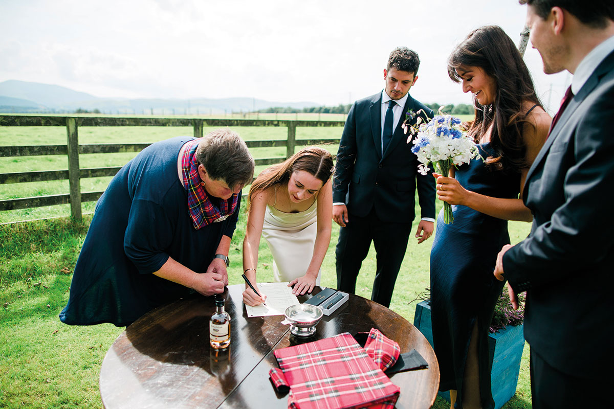 Bride signing marriage schedule with wedding celebrant, two witnesses and groom looking on