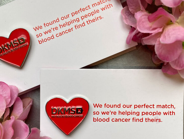 DKMS We Delete Blood Cancer red heart wedding favour pin badge on card place setting