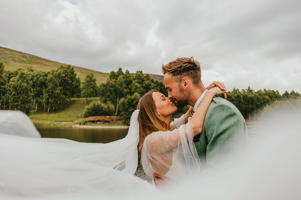 Newlywed bride and groom kissing at Glen Clova Hotel and Lodges