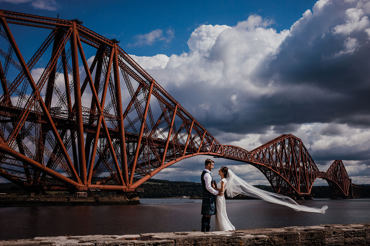 Bride and groom standing by the Forth Rail Bridge at Doubletree Hilton North Queensferry