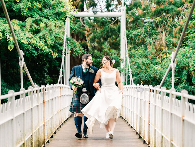bride and groom walking over bridge over River Ness Inverness
