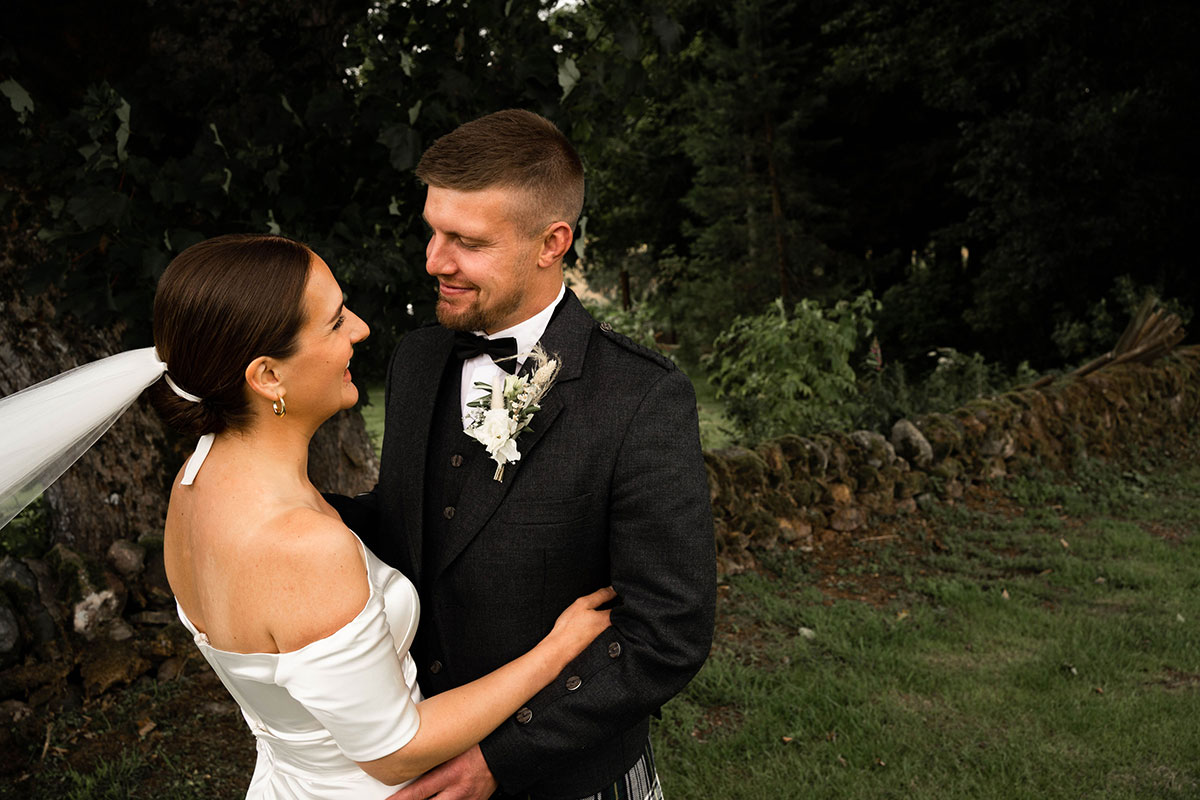 newlywed smiling bride and groom looking into each other's eyes at DIY Perthshire farm wedding