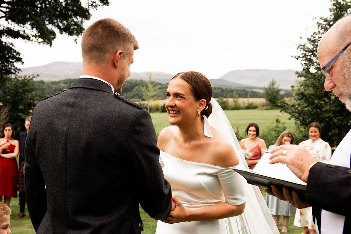 bride laughing and looking at groom during outdoor Perthshire wedding ceremony