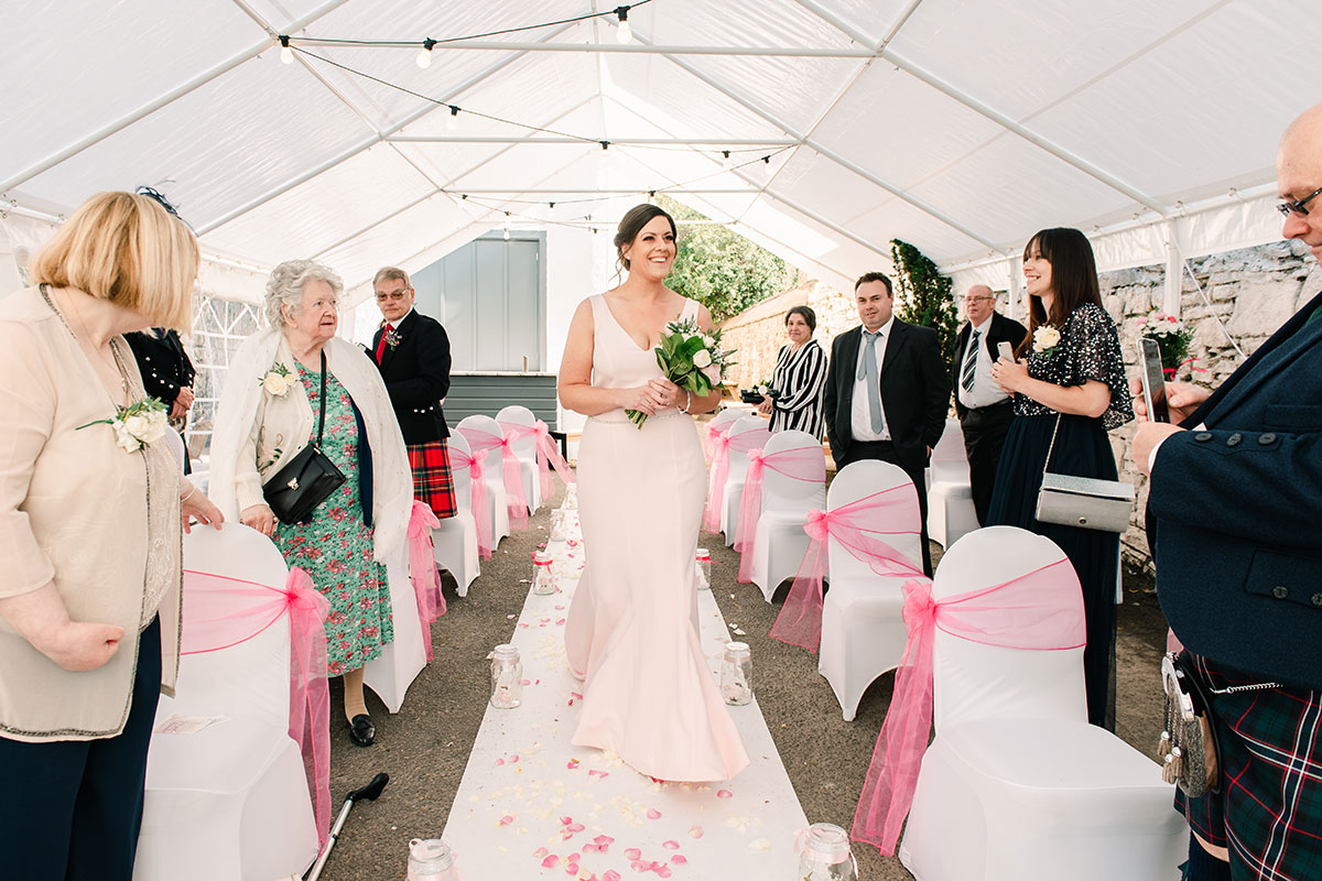 bridesmaid wearing pale pink Milly Bridal dress walking down aisle at marquee wedding ceremony at Waterside Hotel Inverness
