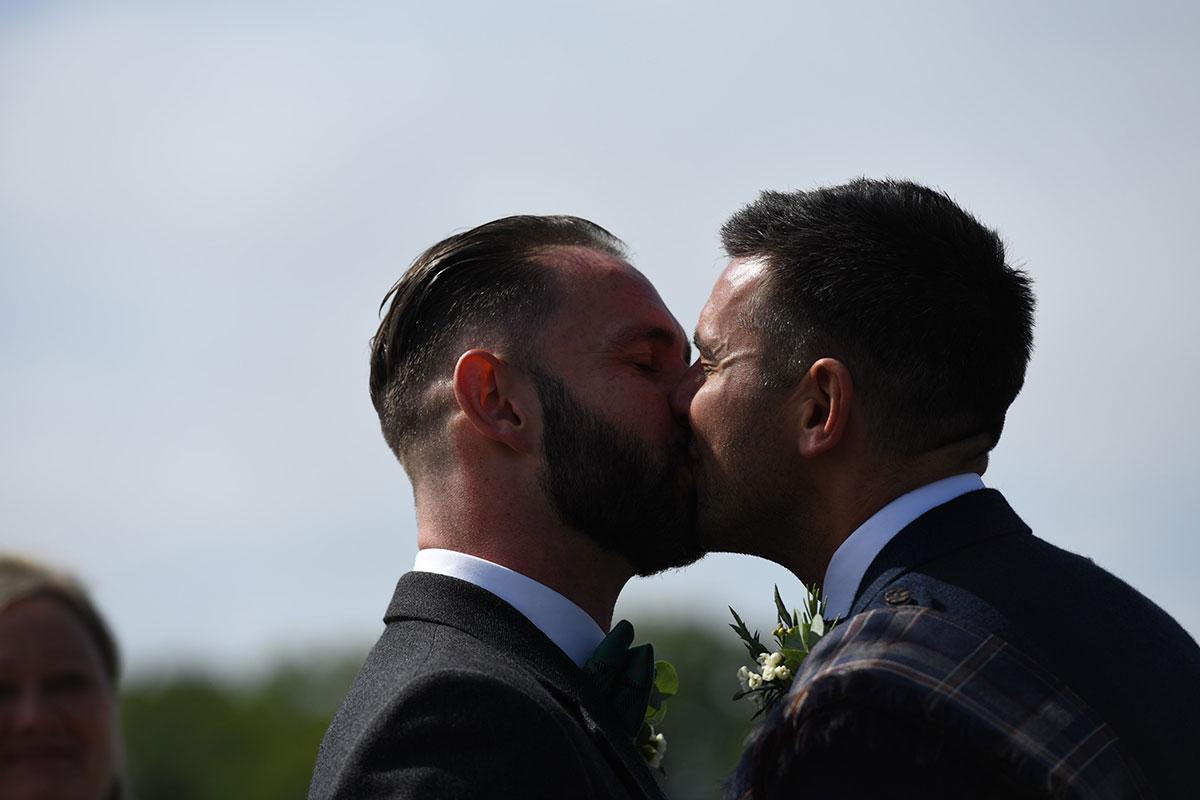 two newlywed grooms kissing at outdoor wedding ceremony at the Gathering