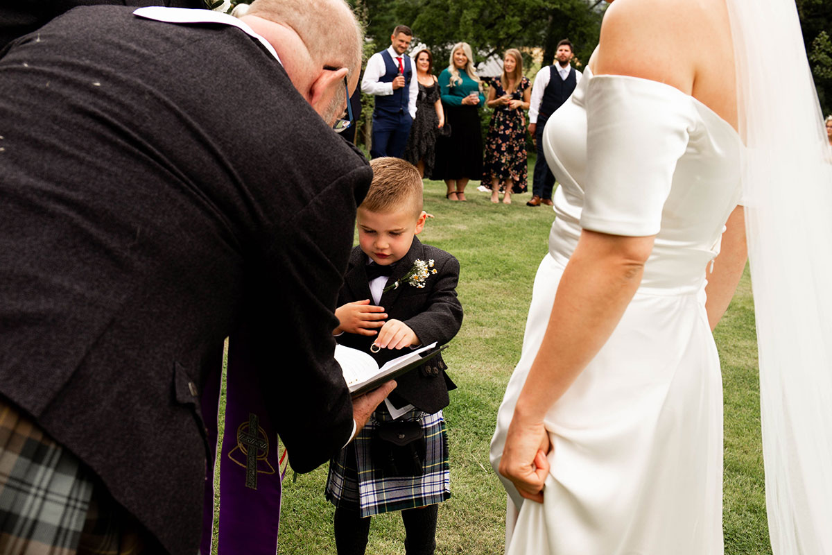 son picking wedding ring from bible in front of bride and minister at outdoor wedding ceremony in Perthshire