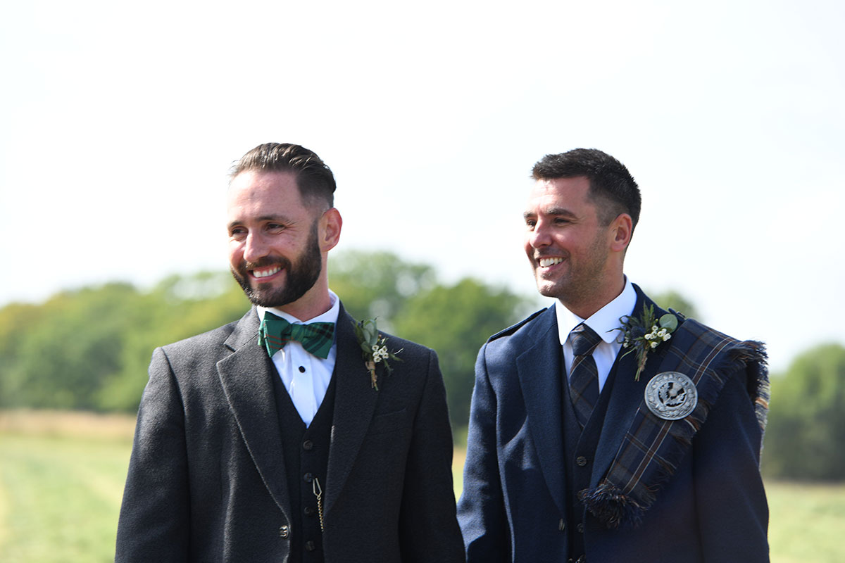 two newlywed grooms wearing Highlandwear smiling outdoors at The Gathering