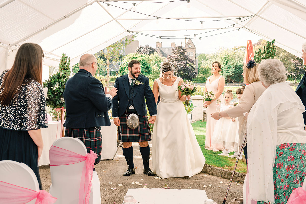 bride and groom surrounded by guests under marquee on the banks of the River Ness Waterside Hotel Inverness