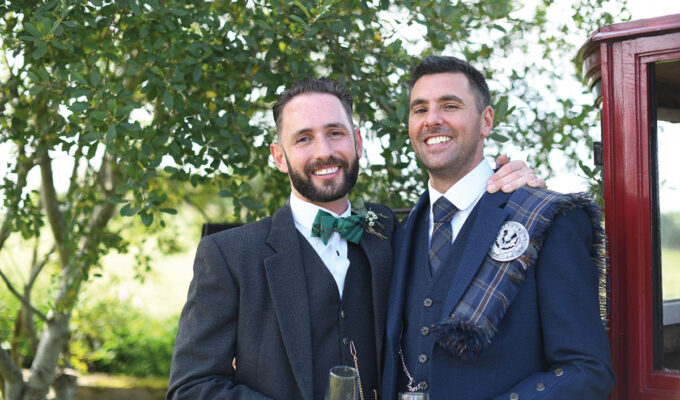 two newlywed grooms wearing Highlandwear smiling outdoors at The Gathering standing next to red carriage