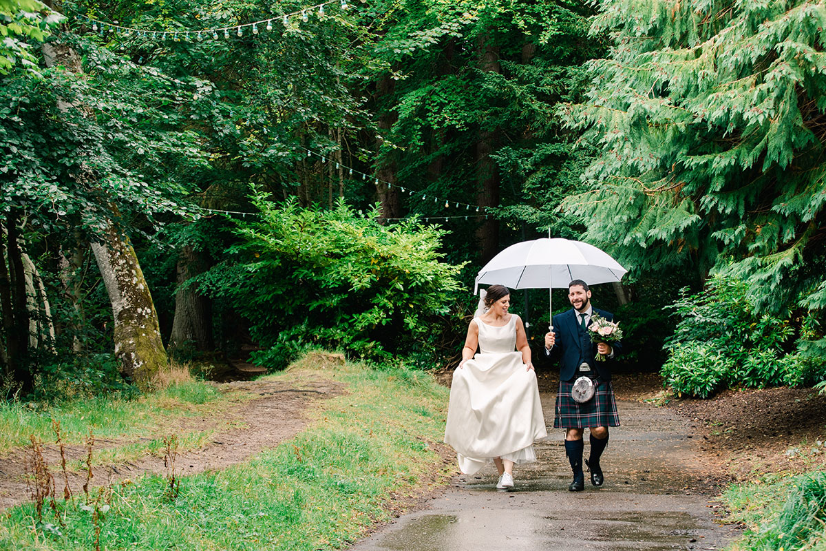 groom carrying brolly and bouquet in the rain at Ness Islands Inverness with bride walking adjacent