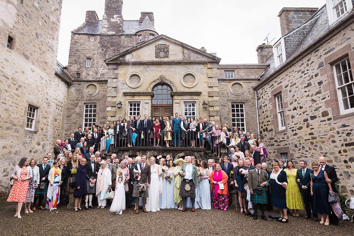 wedding guests posing on stairs in courtyard at Murthly Castle